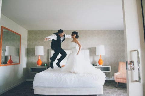newly weds jumping on hotel bed in The Garland Hotel